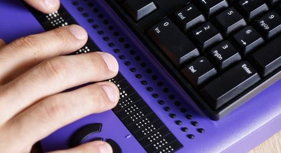 Person nutzt Braille-Zeile von Computer-Tastatur
