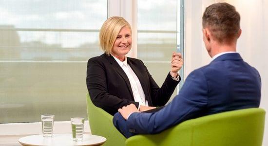 Geschäftsfrau mit Geschäftsmann im Gespräch