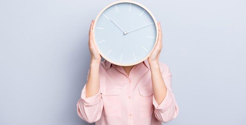 Frau mit Uhr vor dem Kopf - Zeitmanagement